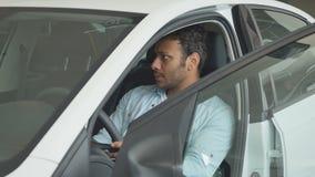 Hombre moreno que examina un coche de lujo en salón auto almacen de video