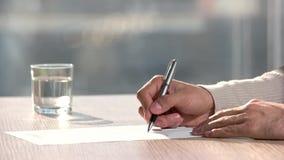 Hombre moreno que firma el contrato profesional en oficina metrajes