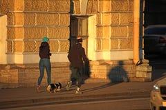 Hombre, mujer, y perro que corre abajo de la calle foto de archivo