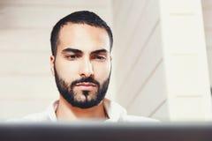 Hombre multicultural barbudo que trabaja con el ordenador portátil imágenes de archivo libres de regalías
