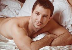 hombre muscular en una cama Imágenes de archivo libres de regalías
