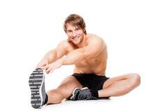 Hombre muscular atractivo que estira en un piso Foto de archivo