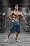 Hombre muscular atractivo que presenta en el gimnasio, abdominal formada ABS desnudo masculino fuerte del torso, resolviéndose Imágenes de archivo libres de regalías