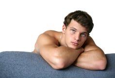 Hombre muscular atractivo que se inclina en el sofá Foto de archivo