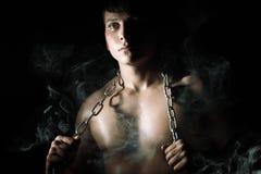 Hombre muscular con el encadenamiento y el humo Foto de archivo libre de regalías