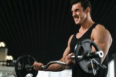 Hombre muscular con el equipo de entrenamiento del peso en el club del gimnasio del deporte fotografía de archivo libre de regalías
