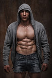 Hombre muscular con la chaqueta abierta que revela el pecho y el ABS musculares Foto de archivo libre de regalías