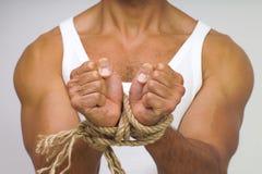 Hombre muscular con las manos atadas por la cuerda Imagen de archivo libre de regalías