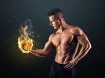Hombre muscular con pesas de gimnasia en fondo negro Fotos de archivo libres de regalías