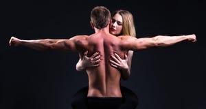 Hombre muscular de abarcamiento de la mujer hermosa sobre gris Fotografía de archivo libre de regalías