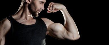 Hombre muscular, demostraciones su bíceps, fondo negro, lugar para el texto a la derecha fotografía de archivo