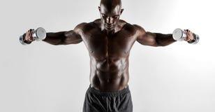 Hombre muscular descamisado que ejercita con los pesos de la mano imagenes de archivo