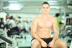 Hombre muscular descamisado que presenta en club de fitness Imagenes de archivo