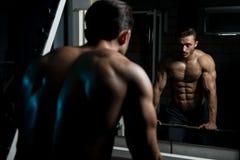 Hombre muscular después del ejercicio que descansa en gimnasio Imágenes de archivo libres de regalías