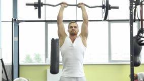 Hombre muscular en el entrenamiento de la fuerza en el gimnasio El atleta hace ejercicio del tríceps con un barbell fotos de archivo