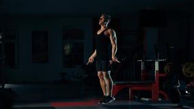 Hombre muscular en el gimnasio, las piernas de entrenamiento que saltan con una cuerda con el concepto de selección de la barra d almacen de metraje de vídeo