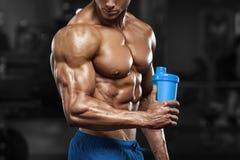 Hombre muscular en gimnasio con la coctelera, abdominal formada ABS desnudo masculino fuerte del torso, resolviéndose Foto de archivo libre de regalías