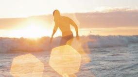 Hombre muscular en nadada de la luz de la puesta del sol en el mar almacen de video