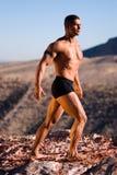 Hombre muscular en roca. Imágenes de archivo libres de regalías