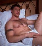 Hombre muscular en una cama Fotos de archivo