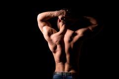 Hombre muscular fuerte que lleva a cabo sus manos detrás de su cabeza Hombros perfectos y músculos traseros Imagenes de archivo
