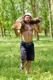 Hombre muscular fuerte que lleva un registro grande de la madera fotografía de archivo libre de regalías