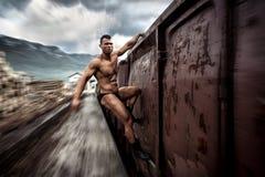 Hombre muscular fuerte que sostiene el tren encendido de mudanza Fotos de archivo libres de regalías