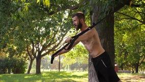 Hombre muscular joven barbudo que hace el entrenamiento que ejercita con los lazos de la aptitud cerca de un árbol cantidad lenta almacen de metraje de vídeo