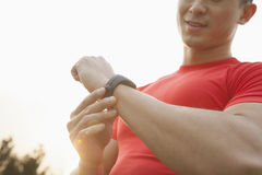 Hombre muscular joven con la camisa roja que mira abajo y que comprueba su reloj, al aire libre en Pekín Imagenes de archivo