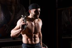 Hombre muscular joven con las cadenas en el gimnasio Imagenes de archivo