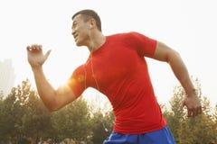 Hombre muscular joven con una camisa roja que corre y que escucha la música en auriculares de botón al aire libre en el parque en  Imágenes de archivo libres de regalías