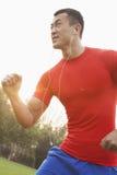 Hombre muscular joven con una camisa roja que corre y que escucha la música en los botones de oído al aire libre en el parque en P Imágenes de archivo libres de regalías