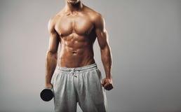Hombre muscular joven descamisado con pesa de gimnasia Foto de archivo