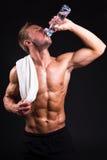 Hombre muscular joven después de entrenar el agua potable de la botella Fotos de archivo libres de regalías