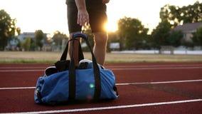Hombre muscular joven en camisas negras que camina con el bolso azul del deporte a disposición corriendo la pista del estadio Ali metrajes