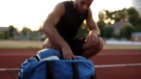 Hombre muscular joven en camisas negras que camina con el bolso del deporte a disposición corriendo la pista del estadio Aliste p metrajes