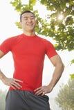 Hombre muscular joven en la situación roja y la sonrisa de la camisa, al aire libre en un parque en Pekín Imagen de archivo libre de regalías