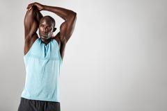 Hombre muscular joven fuerte que estira sus brazos imagenes de archivo