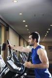 Hombre muscular joven que ejercita en un instructor cruzado en el gimnasio Foto de archivo libre de regalías