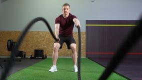 Hombre muscular joven que hace el entrenamiento pesado de la cuerda en el gimnasio almacen de metraje de vídeo