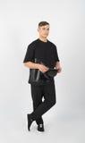 Hombre muscular joven que lleva la ropa negra y el snapback Foto de archivo libre de regalías