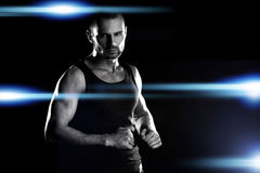Hombre muscular, manos de los corchetes en el puño, en la arena, alrededor del resplandor de los proyectores fotos de archivo