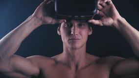 Hombre muscular que consigue experiencia usando los vidrios de las VR-auriculares o de la realidad virtual, colocándose en oscuri almacen de video