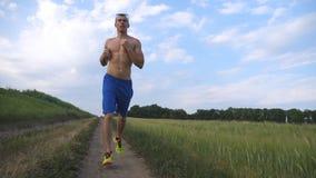 Hombre muscular que corre en la carretera nacional Individuo atlético joven que activa en el rastro rural sobre el campo Entrenam Fotos de archivo