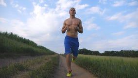 Hombre muscular que corre en la carretera nacional Individuo atlético joven que activa en el rastro rural sobre el campo Entrenam Imágenes de archivo libres de regalías