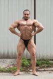 Hombre muscular que dobla los músculos Fotos de archivo