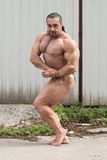 Hombre muscular que dobla los músculos Fotografía de archivo libre de regalías