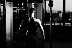 Hombre muscular que dobla los músculos en gimnasio Imagen de archivo libre de regalías