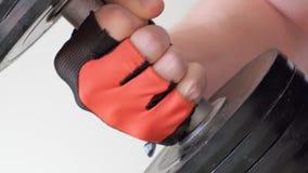 Hombre muscular que dobla su brazo con una pesa de gimnasia en su mano almacen de video