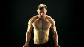 Hombre muscular que ejercita con la banda de la resistencia almacen de video